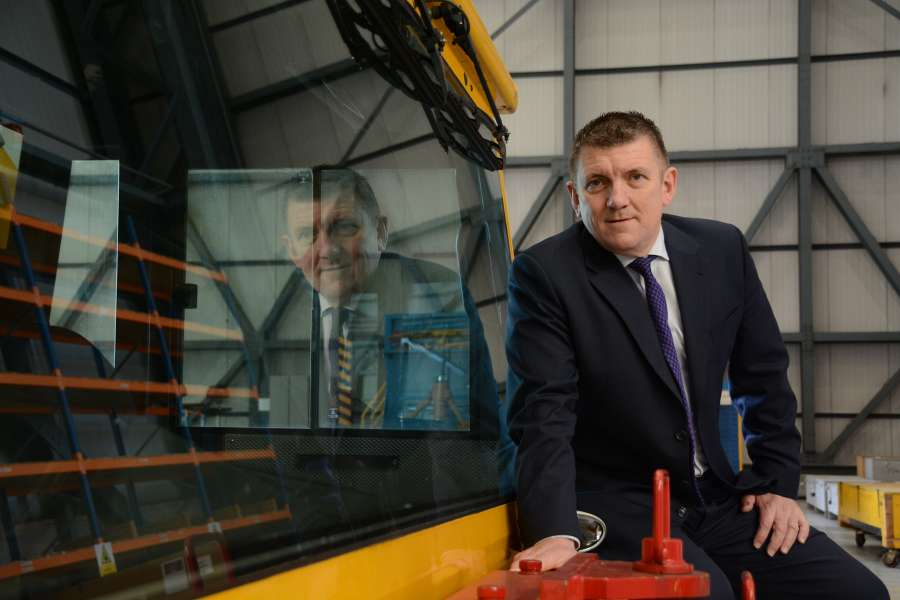 Business Photographers London - Businessman sitting on machinery