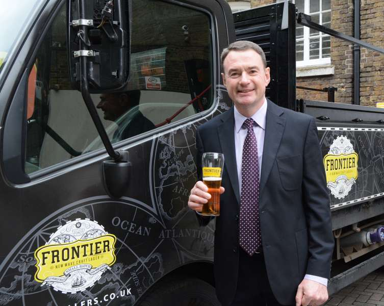 Corporate Photographers London - Businessman holding a pint of ale next to a delivery truck