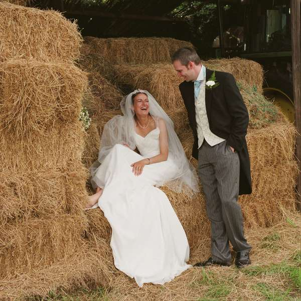 Wedding Photographers London - Bride and groom on hay bales
