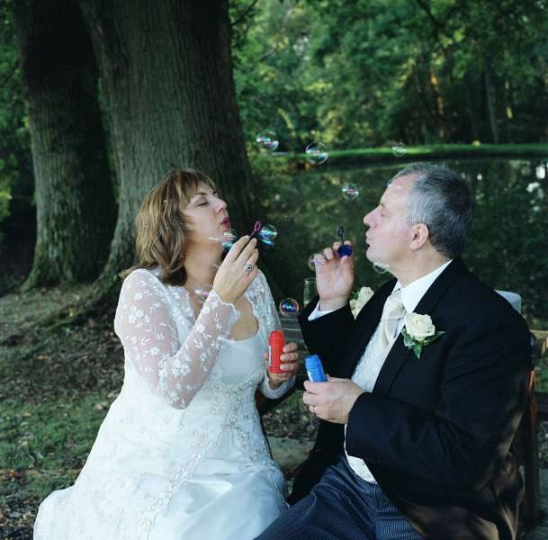 Wedding Photographers London - Bride and groom blowing bubbles